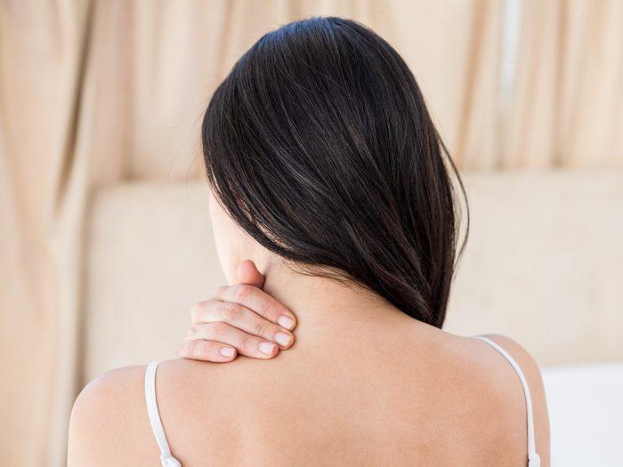 Health symptoms you should never ignore - woman rubbing stiff neck