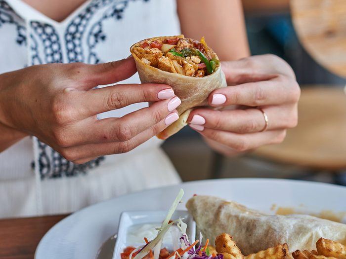 Nutritionists never order - Female hands holding tasty mexican burrito with different ingredients inside. Woman eating delicious pita and salad with French fried potato.