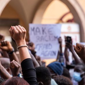Racism quotes - People raising fist with unfocused background in a pacifist protest against racism demanding justice