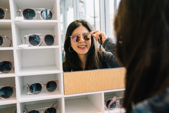 Sunglasses myths - Woman trying on glasses in store