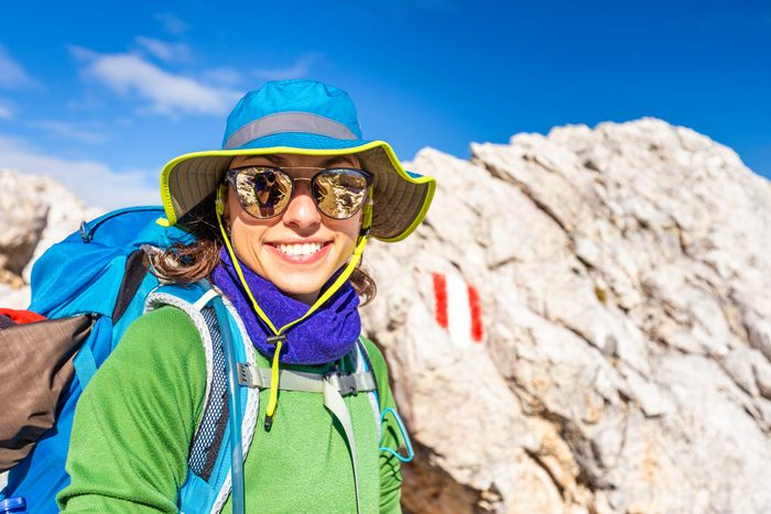 Sunglasses myths - Woman backpacker hiking with sunglasses