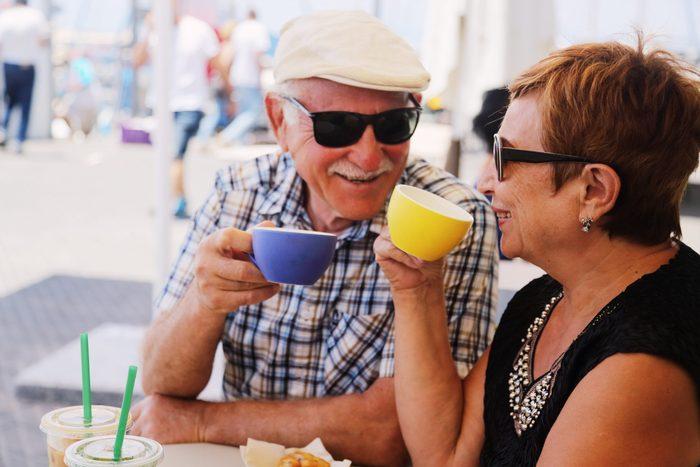Sunglasses myths - Senior couple drinking coffee outside