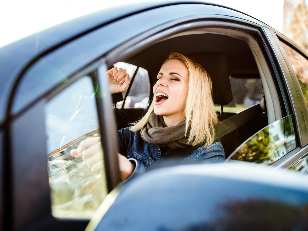 Woman singing in car while driving