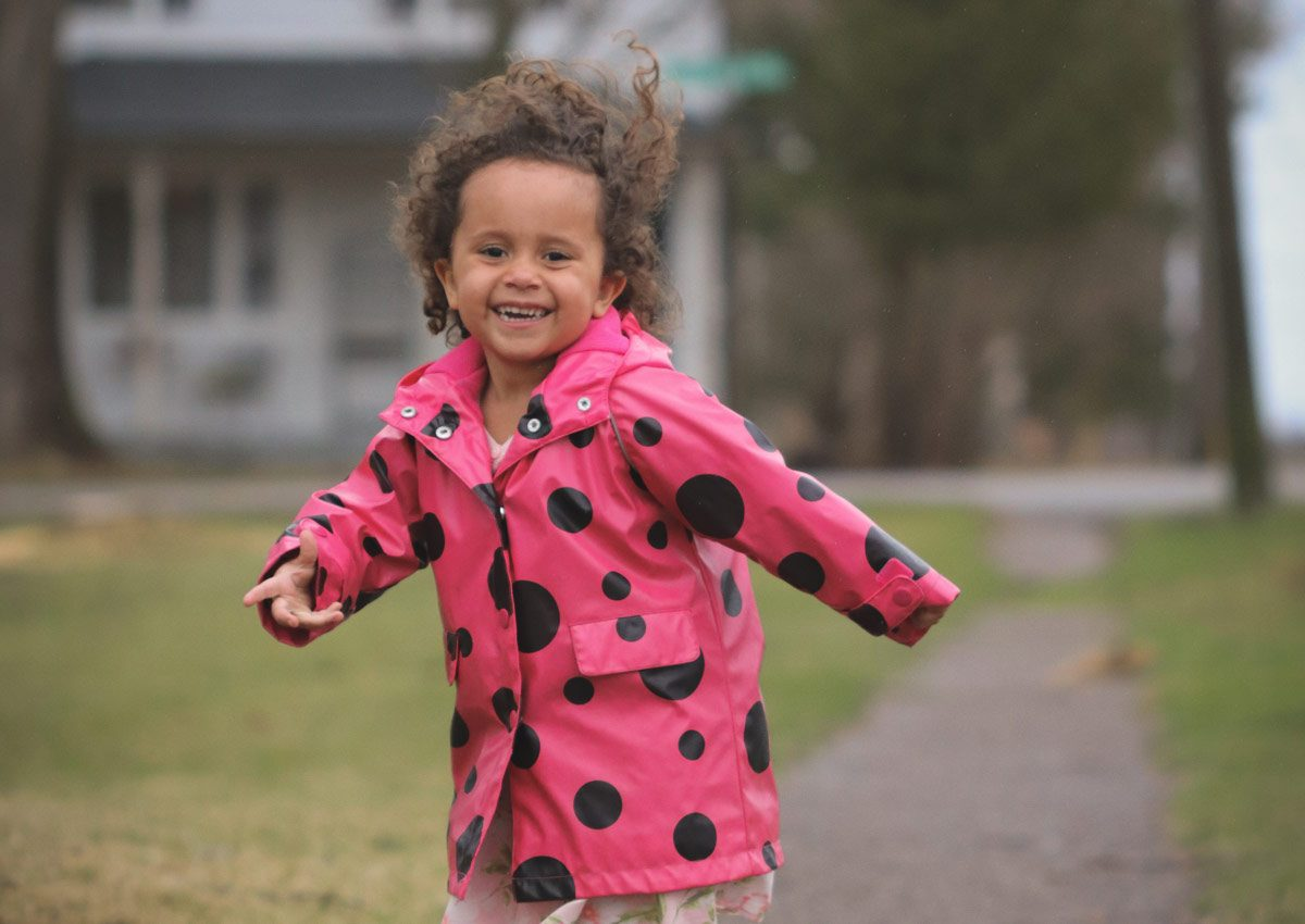 Cute little girl smiling and laughing while running on a sidewalk
