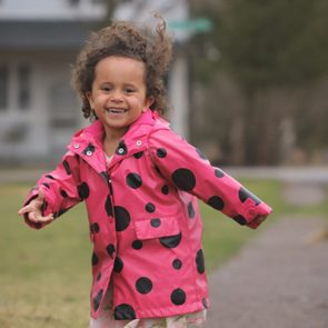 What I'm thankful for - Cute little girl smiling and laughing while running on a sidewalk