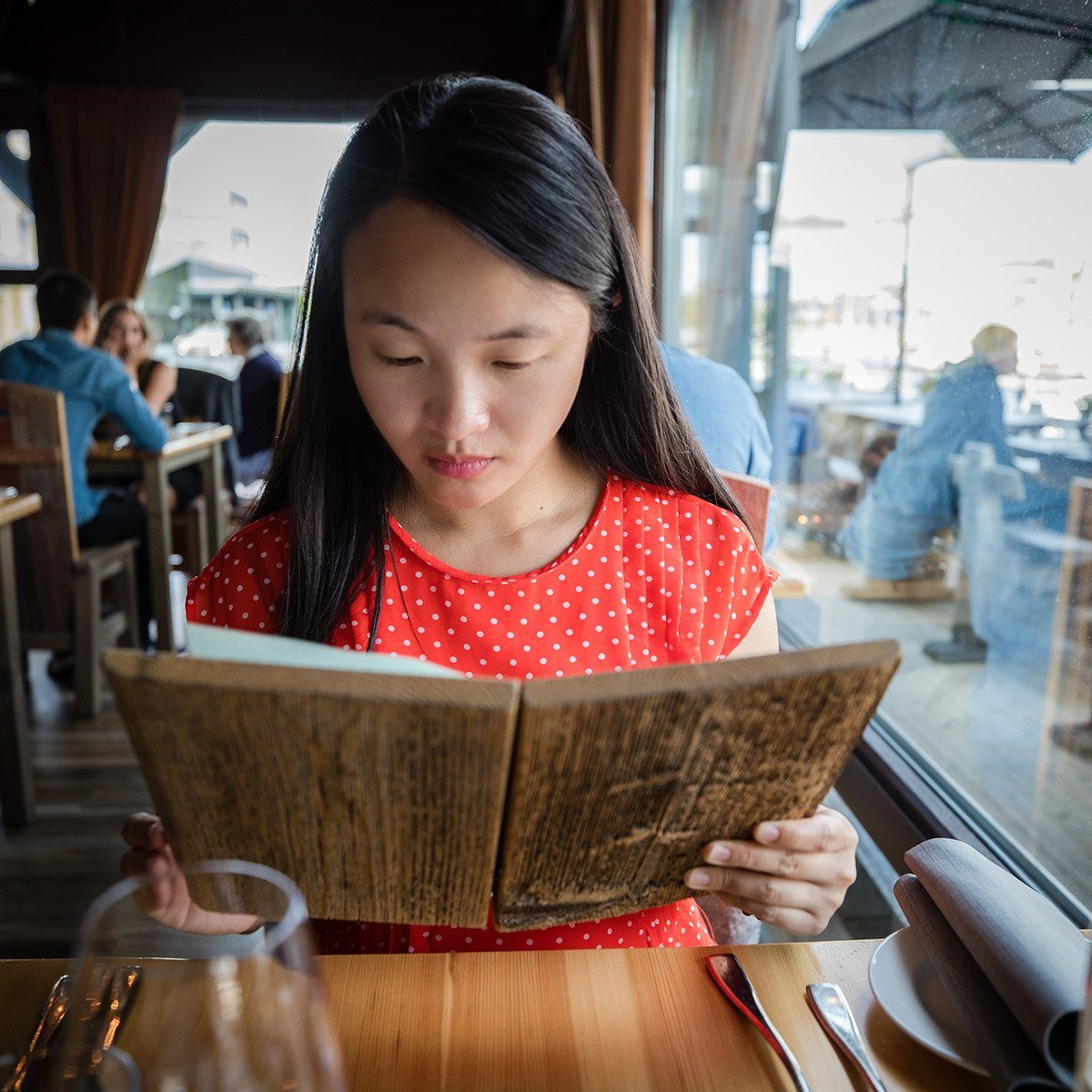 A young Chinese woman is carefully reading the menu made of wood at a restaurant on a fine day in Trondheim, Norway.