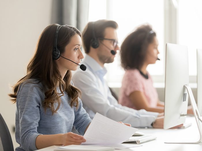 Work jokes - Diverse call center workers sitting in row, focus on customer service member girl in headset looks at pc screen hold paper talk with potential client provide insurance information sell company product