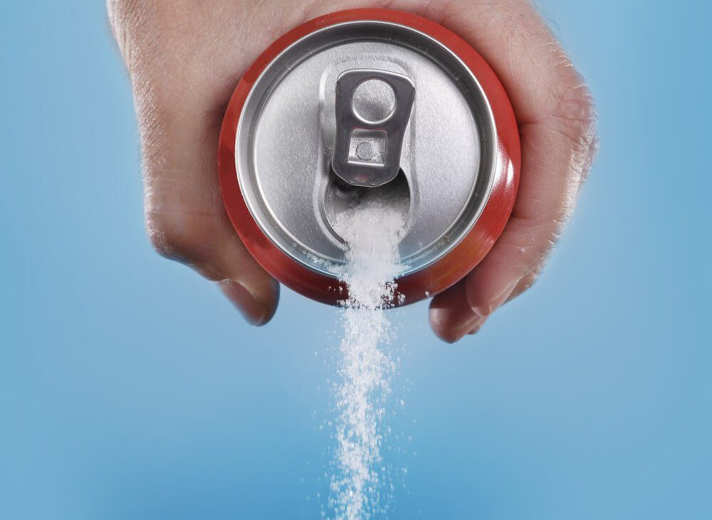 hand holding soda can pouring a crazy amount of sugar in metaphor of sugar content of a refresh drink isolated on blue background in healthy nutrition, diet and sweet addiction concept