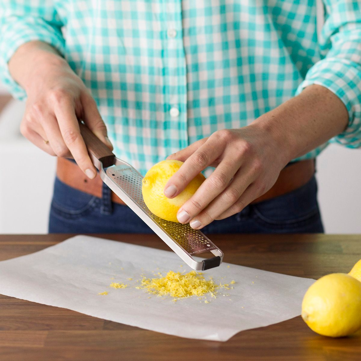 Person using a microplane to zest a lemon