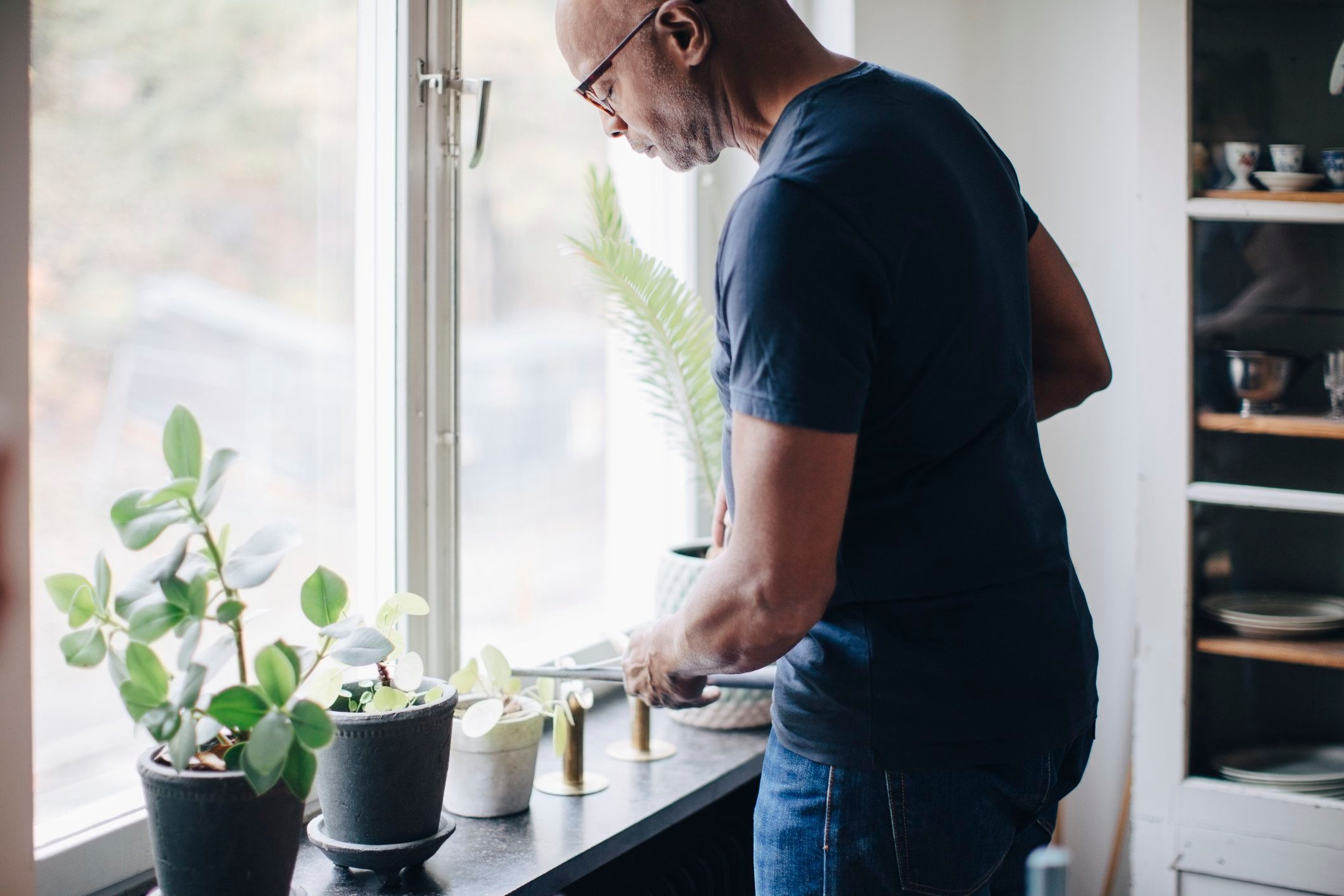 man watering plants in house
