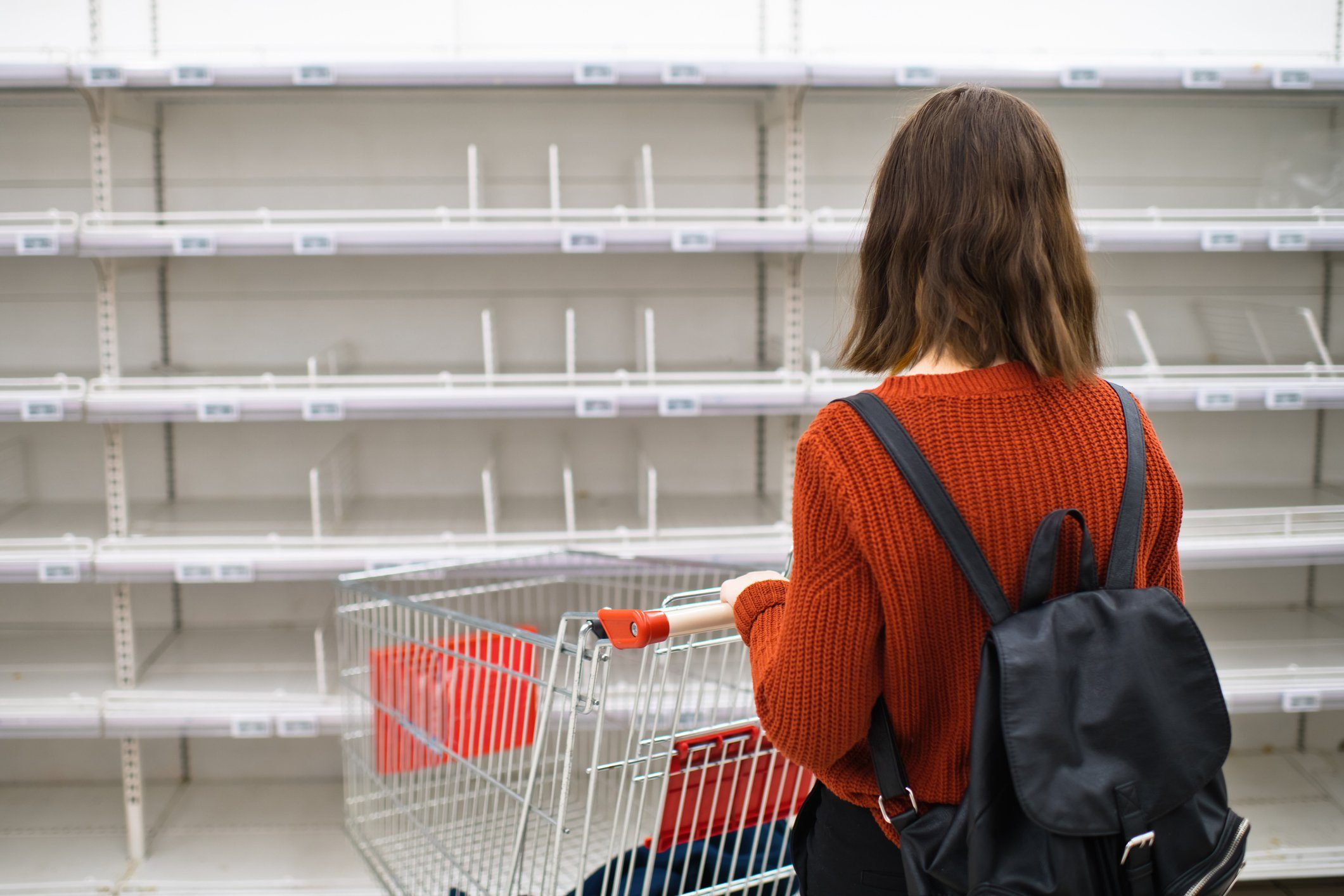 Young girl in front of empty shelf in a supermarket, panic buying and hoarding concept