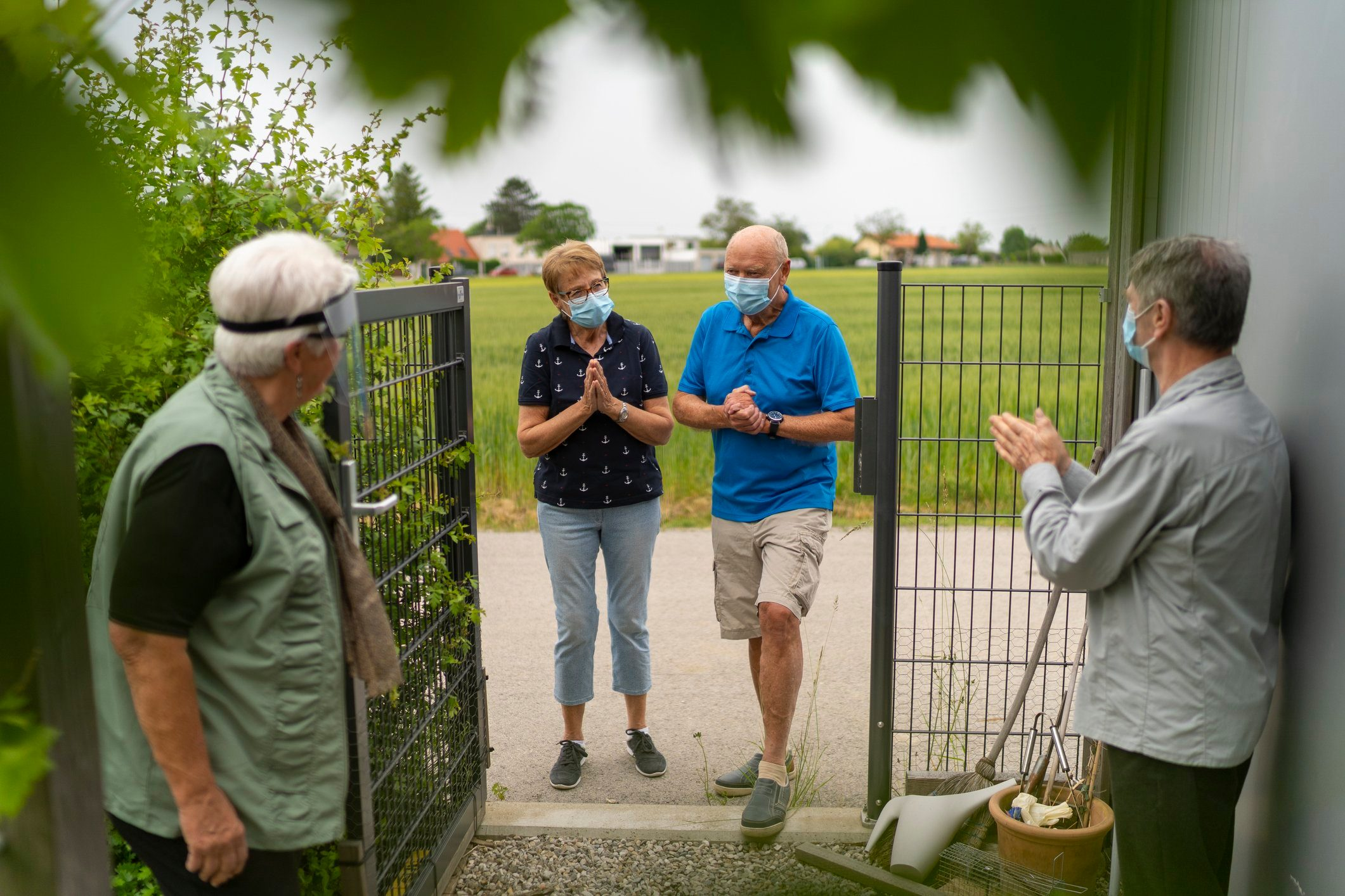 seniors visiting at garden fence door, new greetings in times of coronavirus