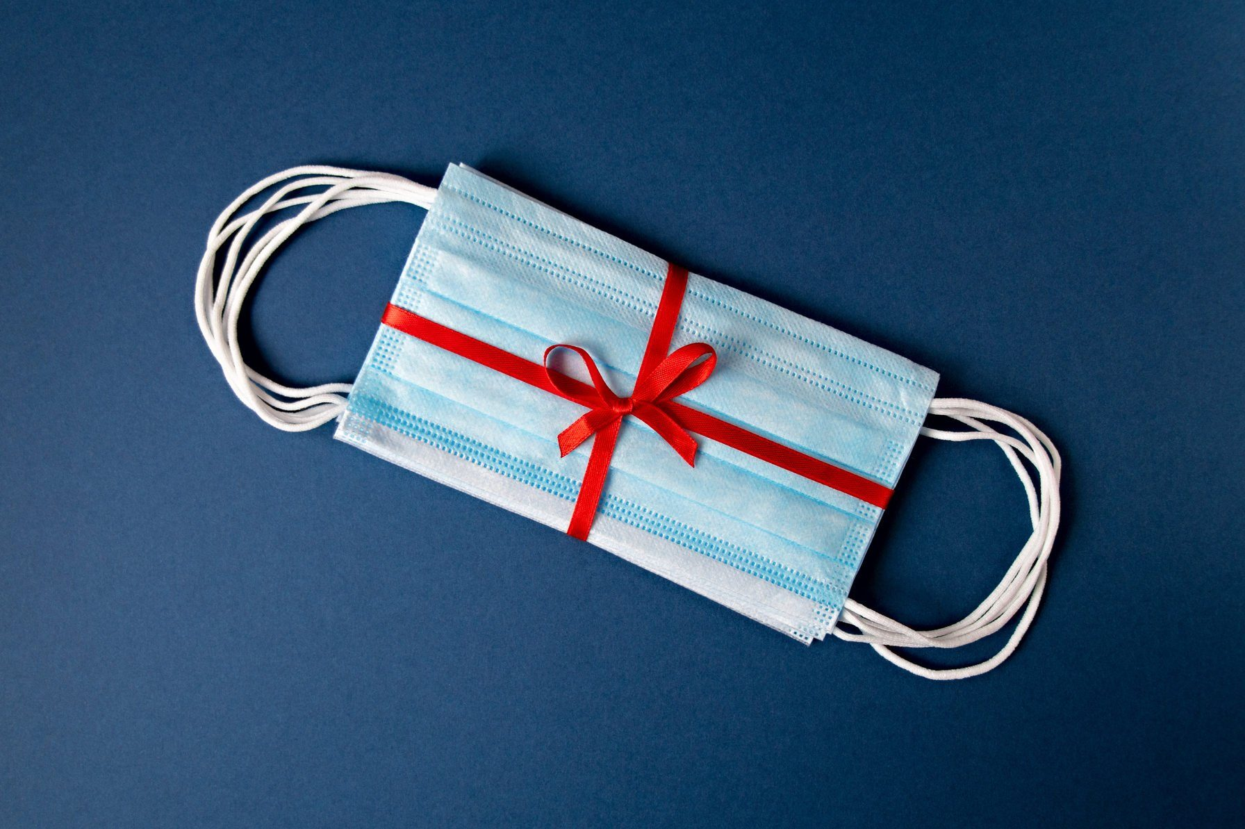 Top view medical protective masks with red ribbon on a blue background with copy space
