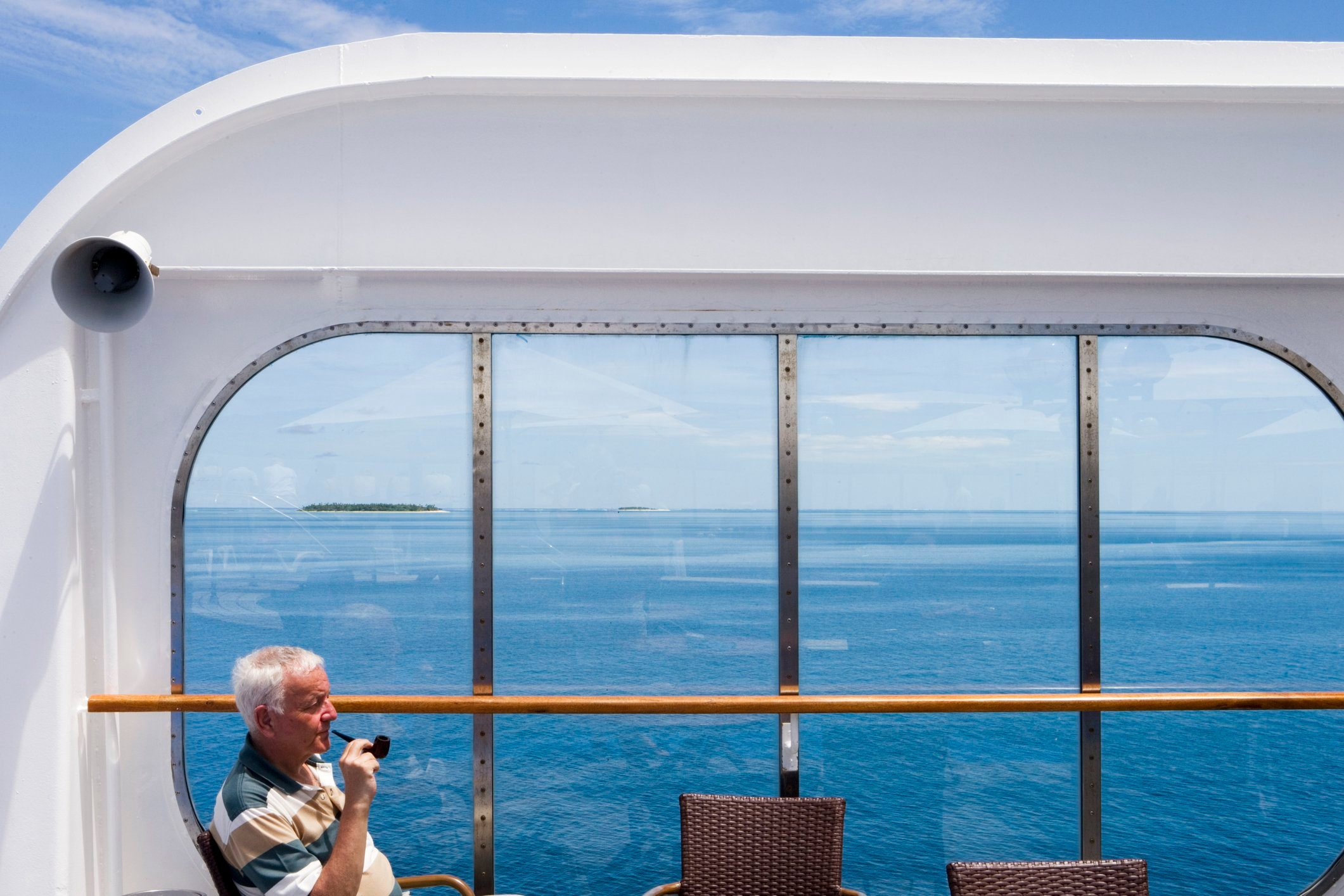 Man enjoys pipe aboard cruiseship MV Columbus (Hapag-Lloyd Cruises) during passage through islands of Mamanuca Group.