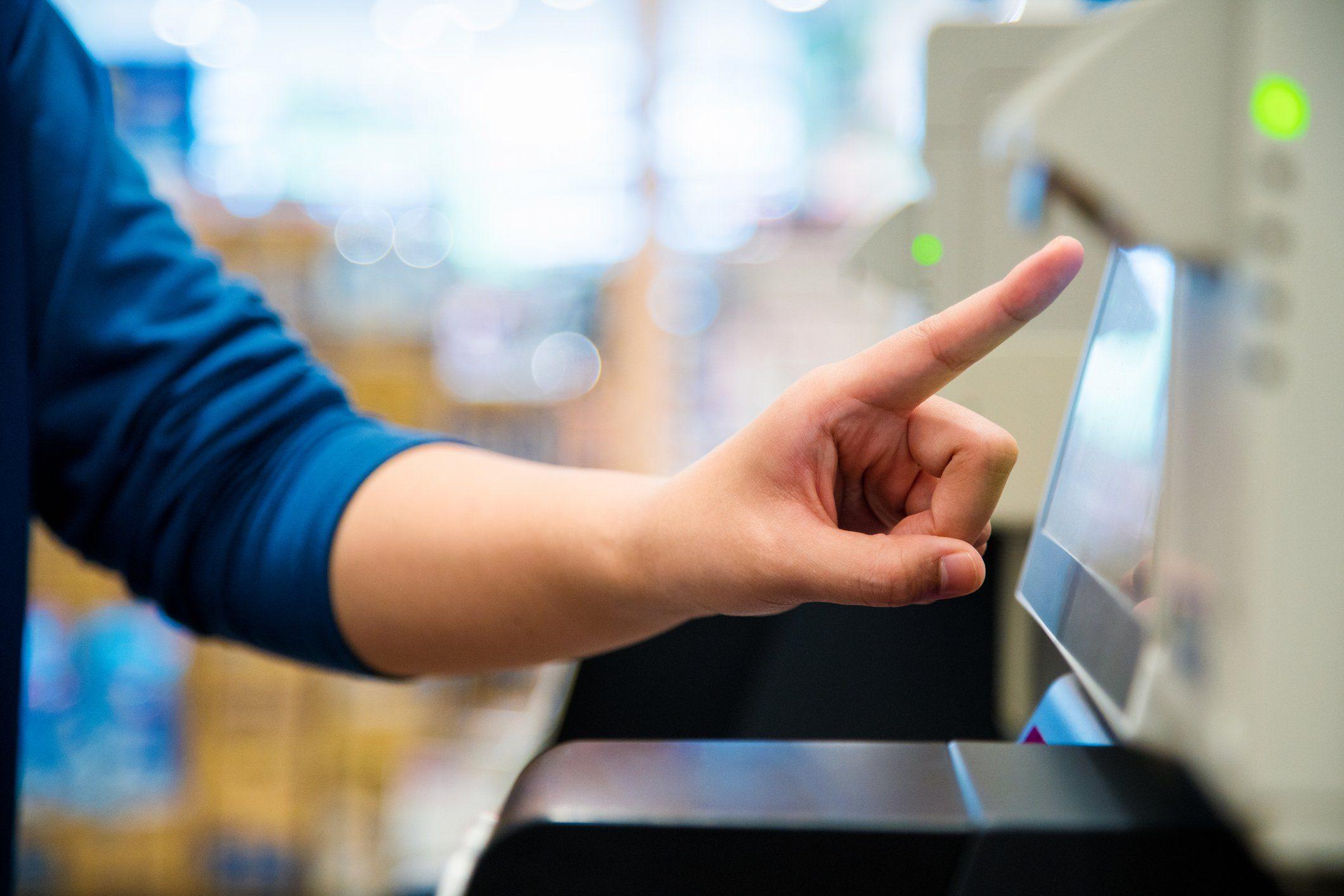 Close up of a woman using a self checkout machine