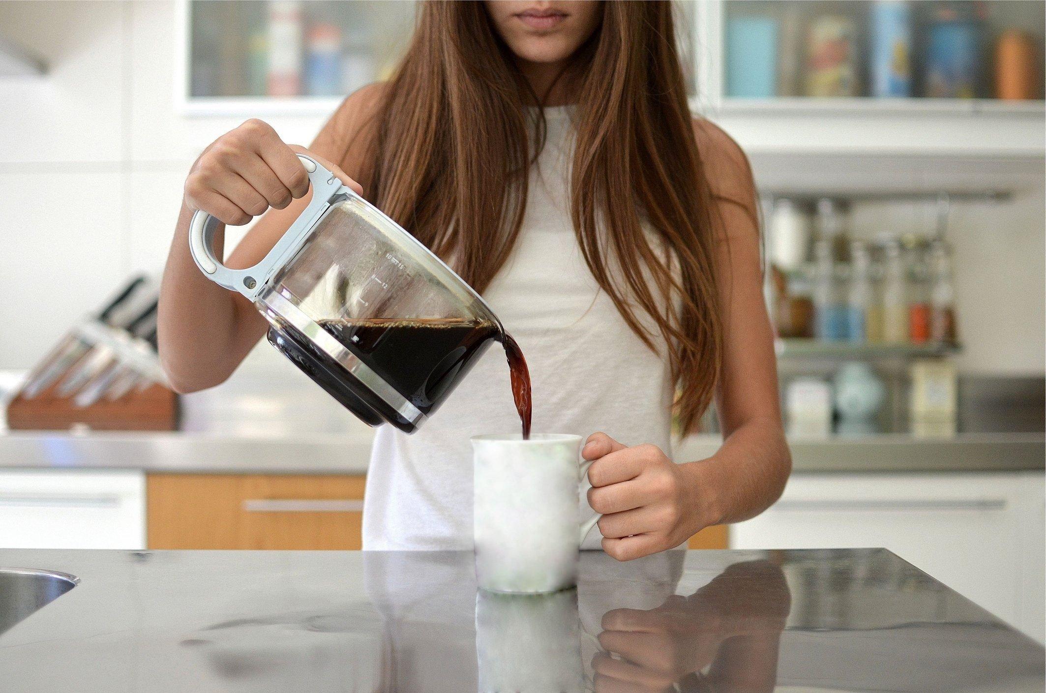 woman pouring coffee into mug
