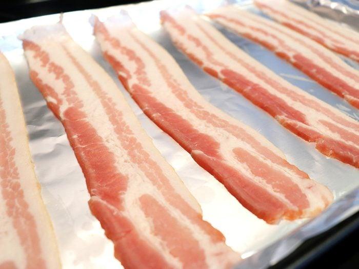 Bacon tips - raw bacon sliced on aluminum foil for baking