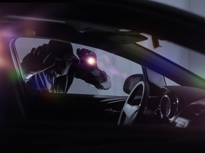 Car anti-theft devices - car thief looking in car with flashlight