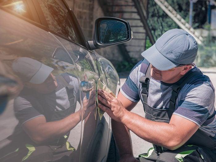 Car paint repair - man inspecting car paint job