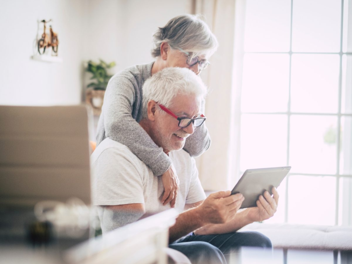 Senior couple using the laptop together at home in the kitchen - Covid