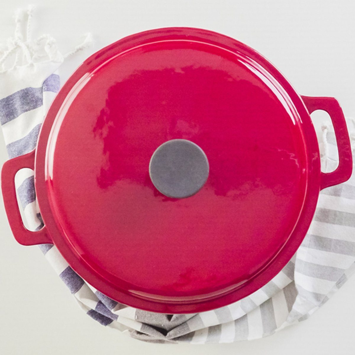 Brand new enameled cast iron covered dutch oven on a white background.