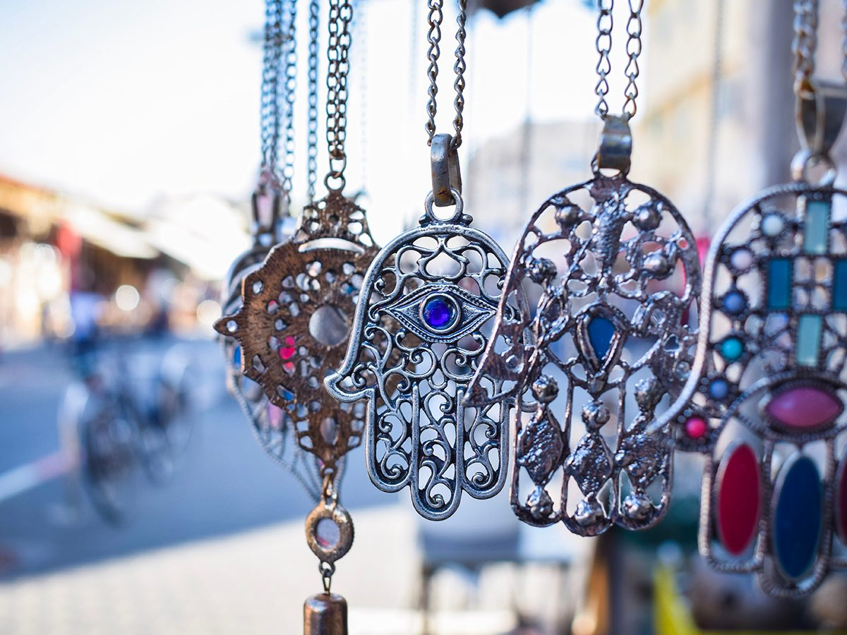 Close-up of Hamsa, also known as Fatima Hand or Hand of God necklace, pending on a flea market in Tel Aviv-Jaffa, Israel. Metal protection amulets