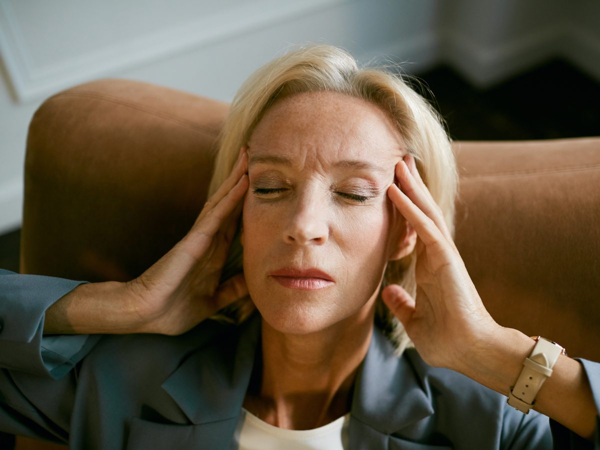 Middle-aged woman experiencing a migraine