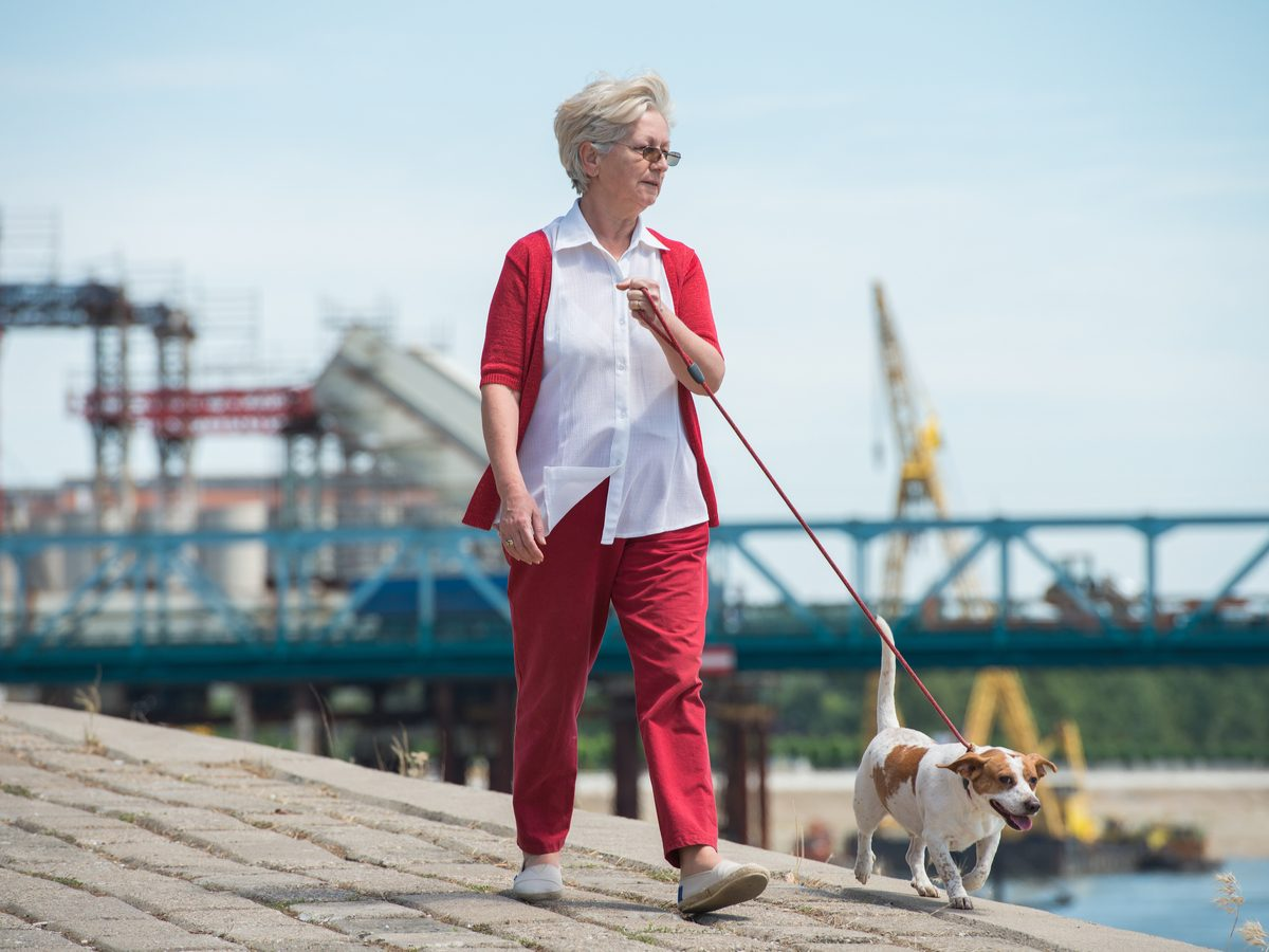Senior woman walking her dog along the pier