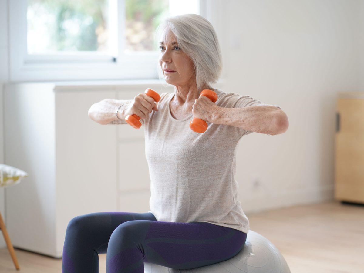 Senior woman lifting weights at home