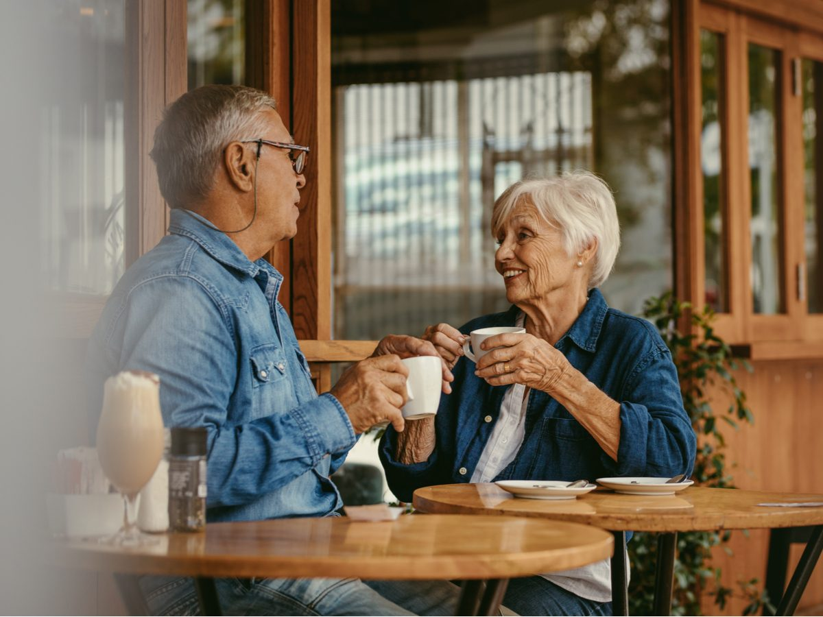Two seniors having a conversation in a cafe