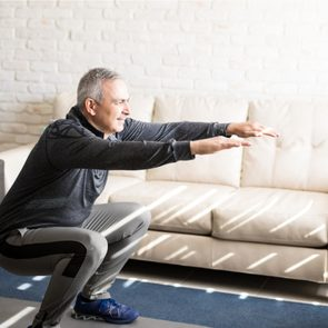 Middle-aged man stretching in his living room
