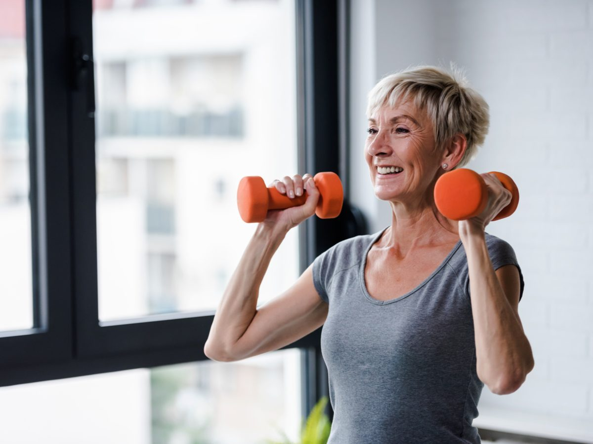 Woman lifting weights in her condo