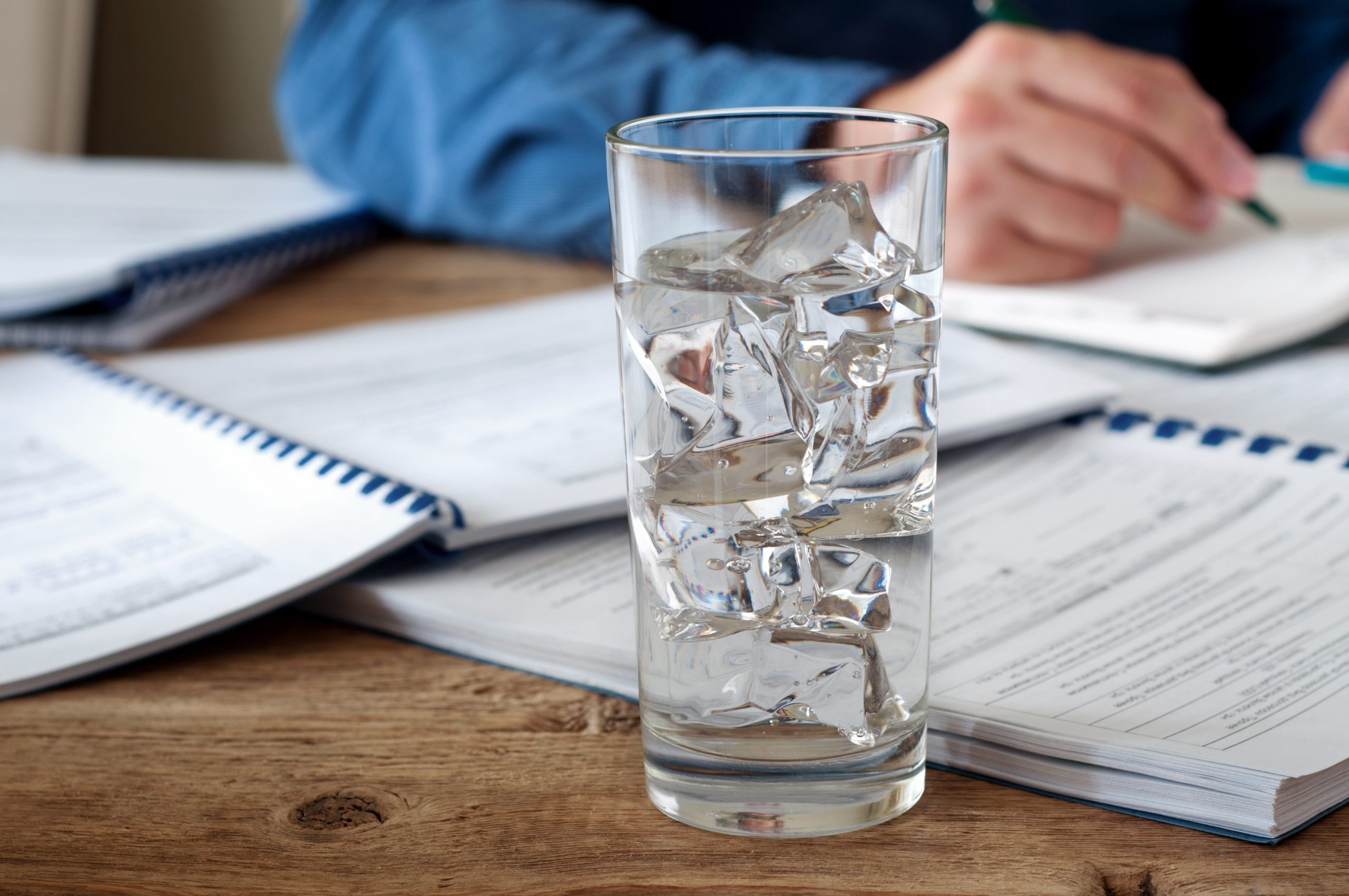 Glass of water with ice on a wooden office table. Against the background of a glass of water running man. Copy space