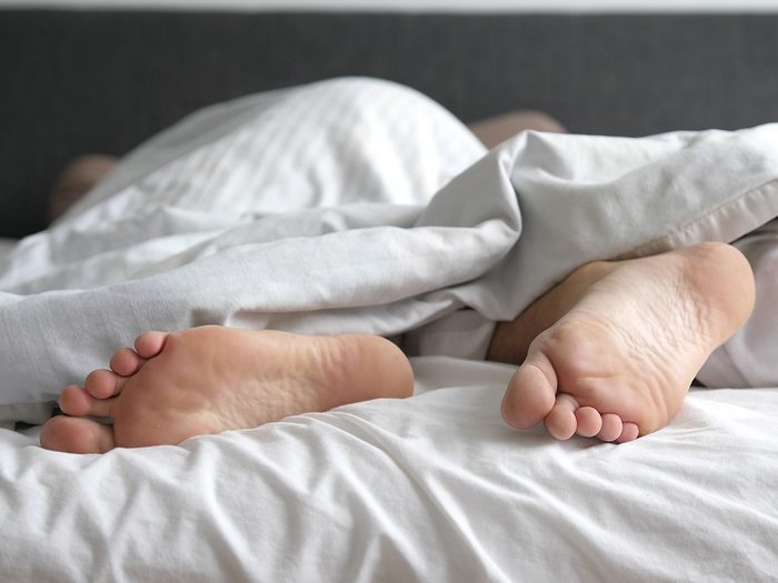 Medical reasons you're tired all the time - Man sleeping in bed feet relax on holidays. Close up of men feet