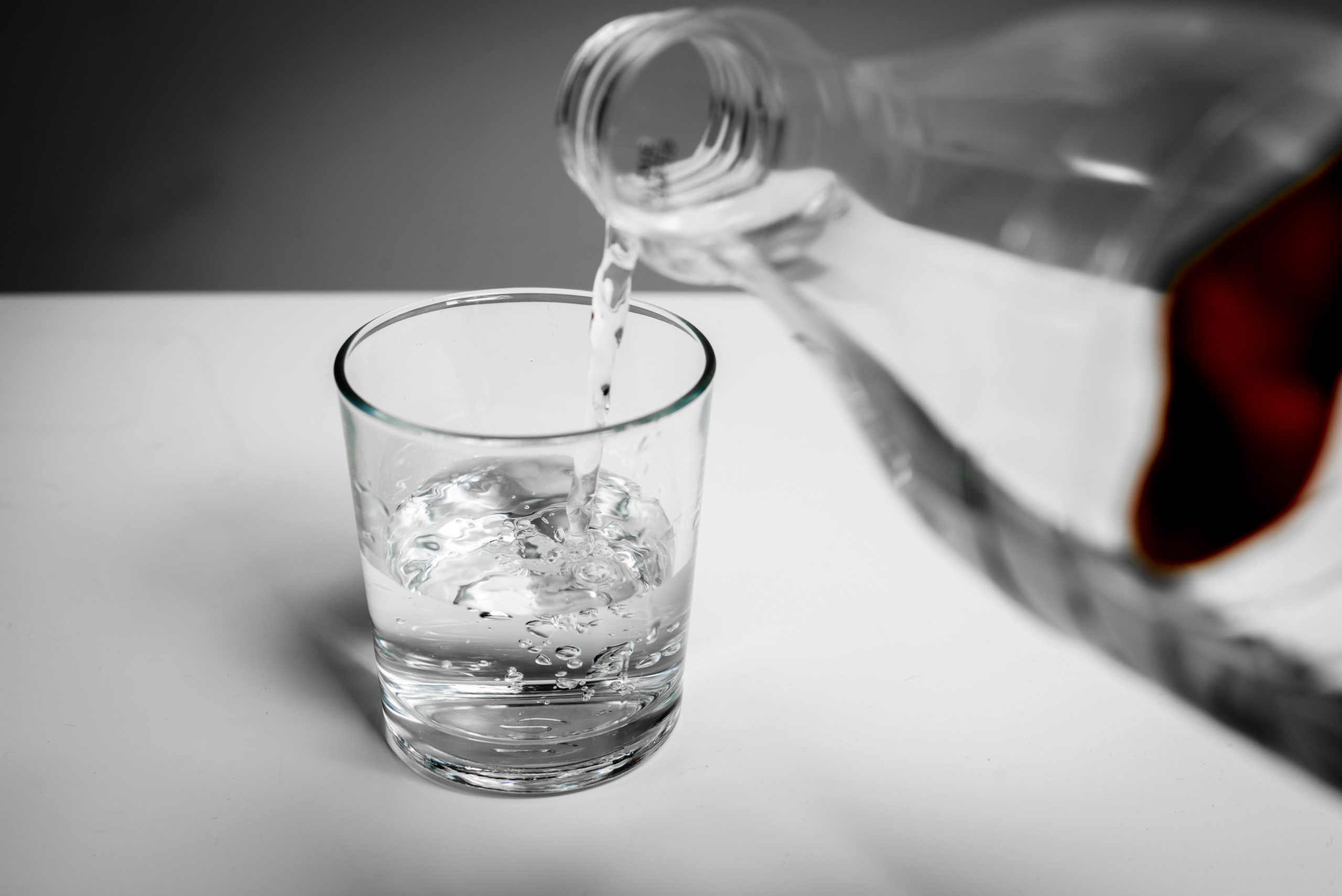 Pouring water into a glass from a bottle. The price is rising. Quenches thirst. Problems with water in some countries.The glass is filled with water.
