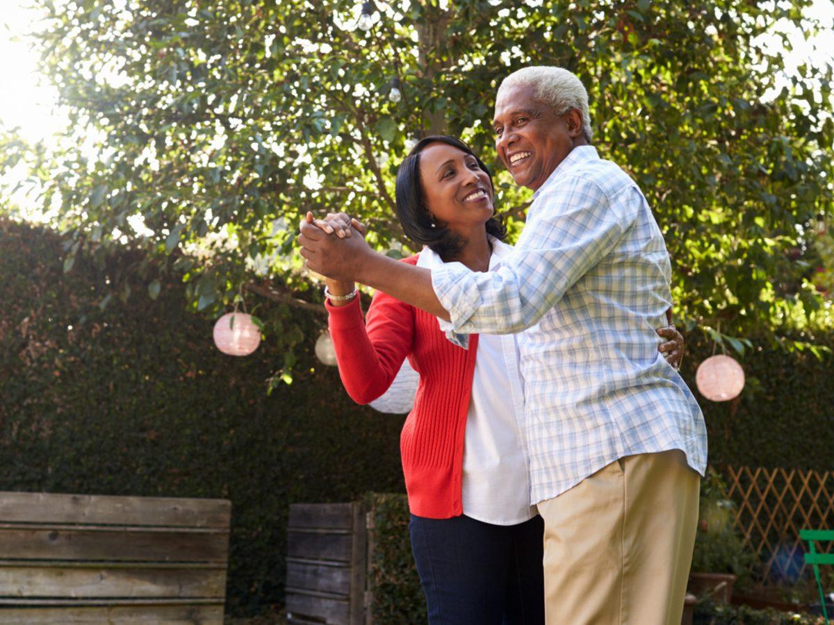 Elderly couple dancing in their backyard