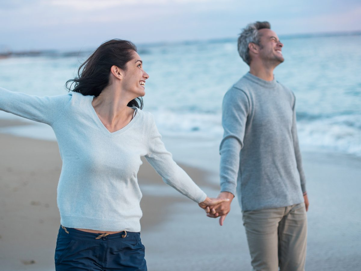 Middle-aged couple walking on the beach at sunset