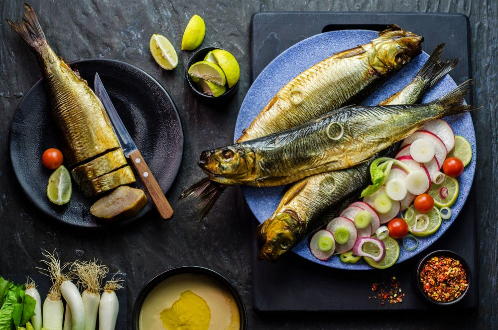 Mediterranean food, smoked Herring fish served with green onion,lemon,cherry tomatoes,spices,bread and Tahini sauce on dark background.Top view with close-up