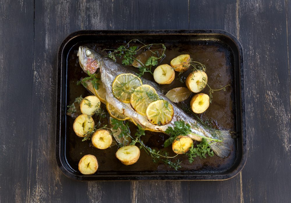 Delicious baked rainbow trout straight from the oven with potato, lemon and herbs.