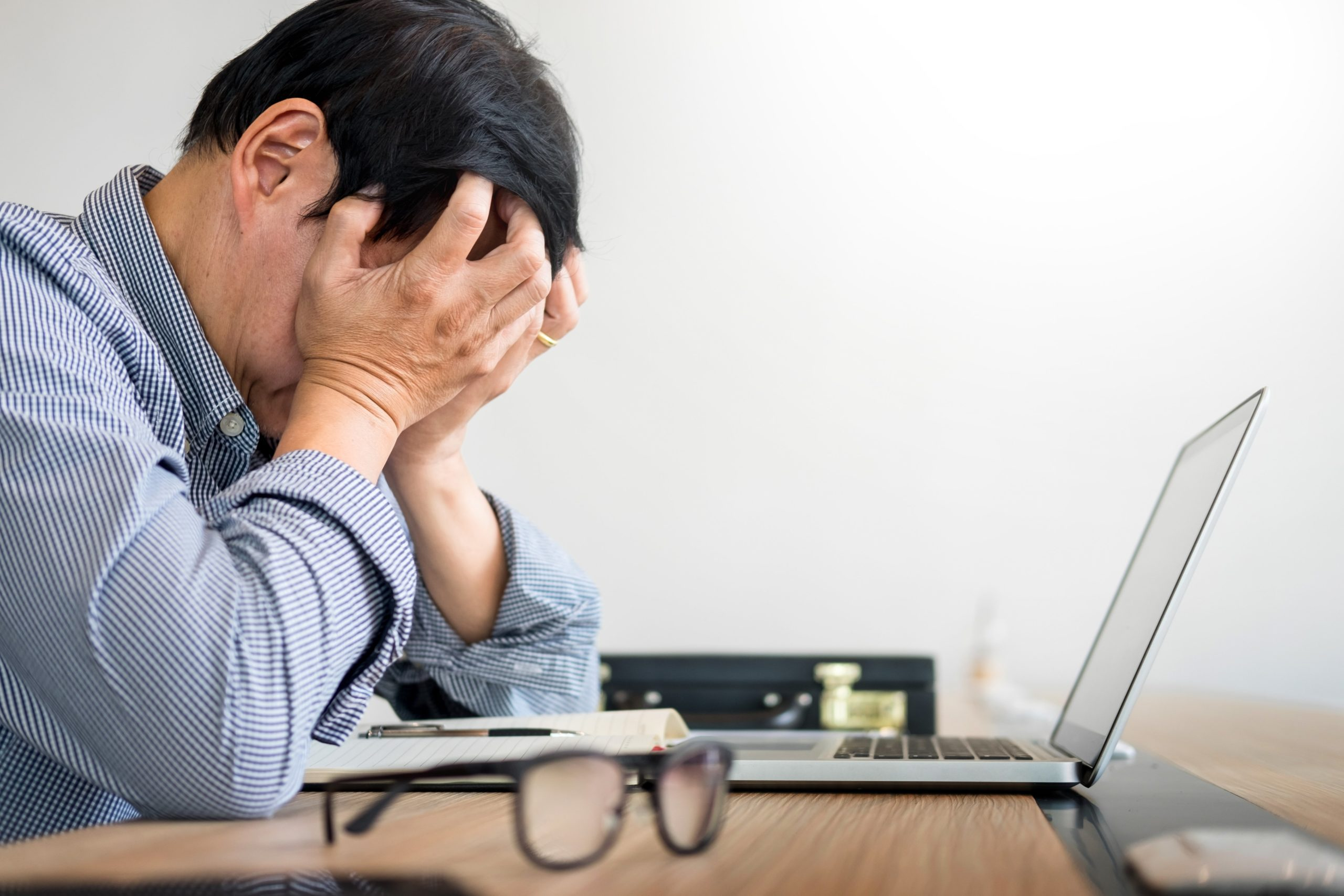 Stressed businessman Feeling sick and tired while sitting at laptop