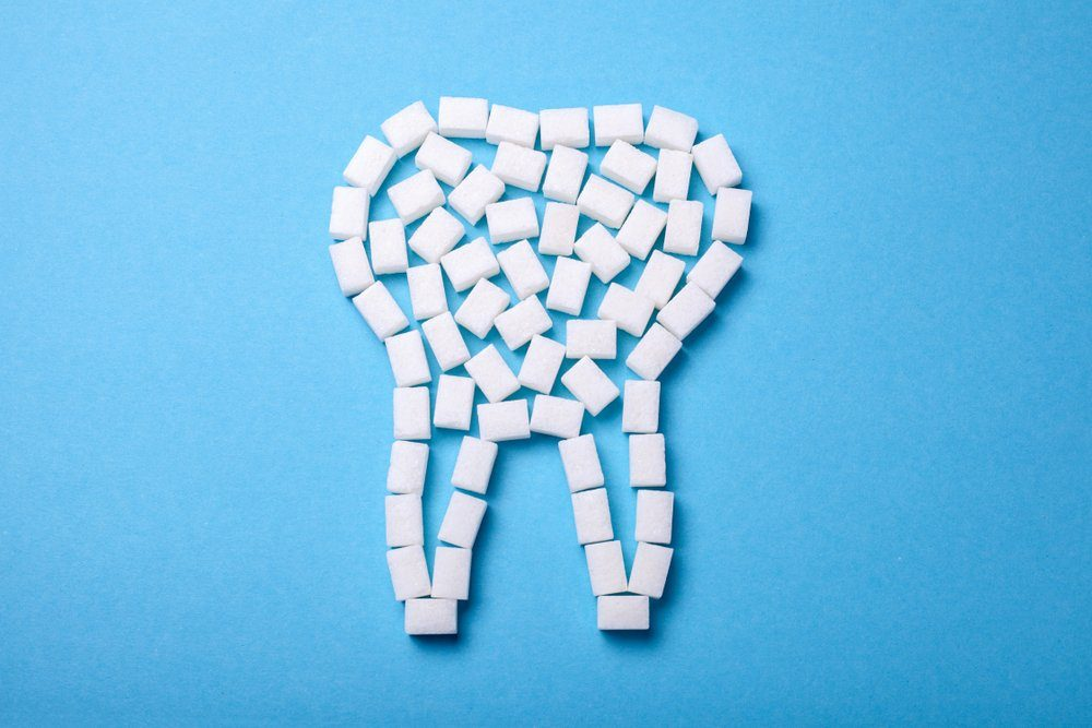 Sugar destroys the tooth enamel and leads to tooth decay. Sugar cubes are laid out in the form of a tooth on a blue background.