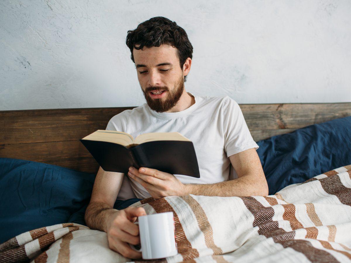 Bearded man reading aloud in his bedroom