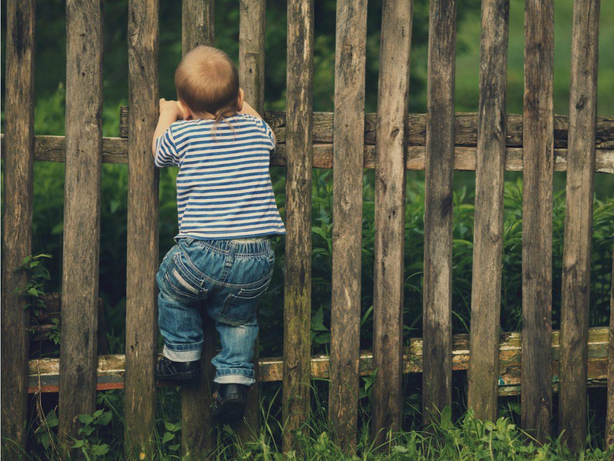 Little boy climbing a wooden fence