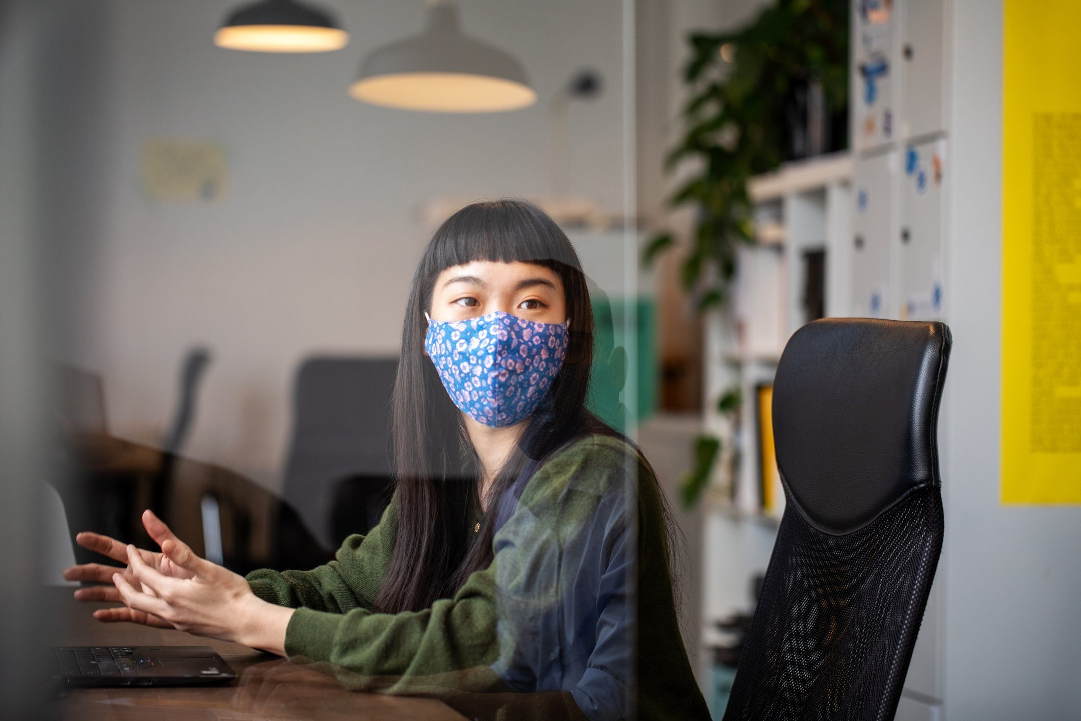 Businesswoman discussing work with colleague through glass shield on desk