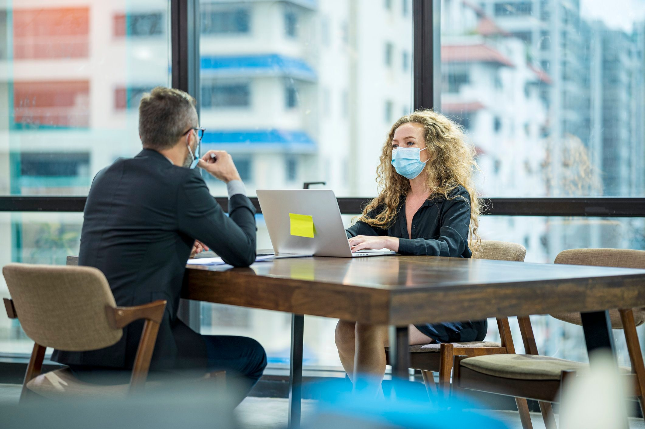 Colleagues decision together in the skyscraper office. They are wearing medical face mask during spread of virus.