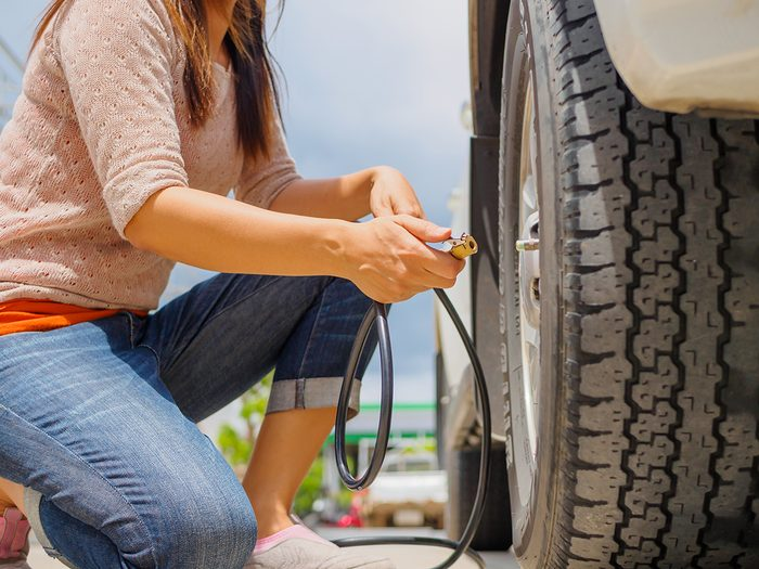 Car tire maintenance - driver checking air pressure and filling air in the tires close up