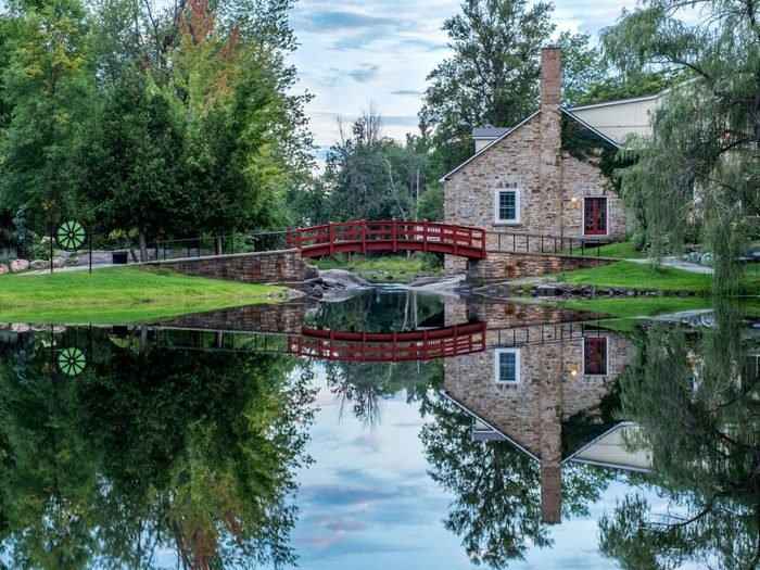 Day trips from Ottawa - In Stewart Park, a view of the red footbridge and old stone house surrounded by trees, as they are reflected in the perfectly still pond