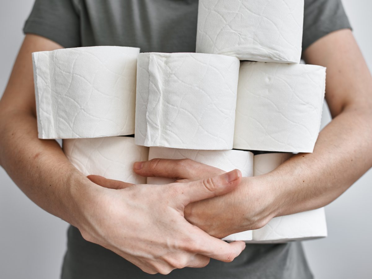 Man holding several rolls of toilet paper