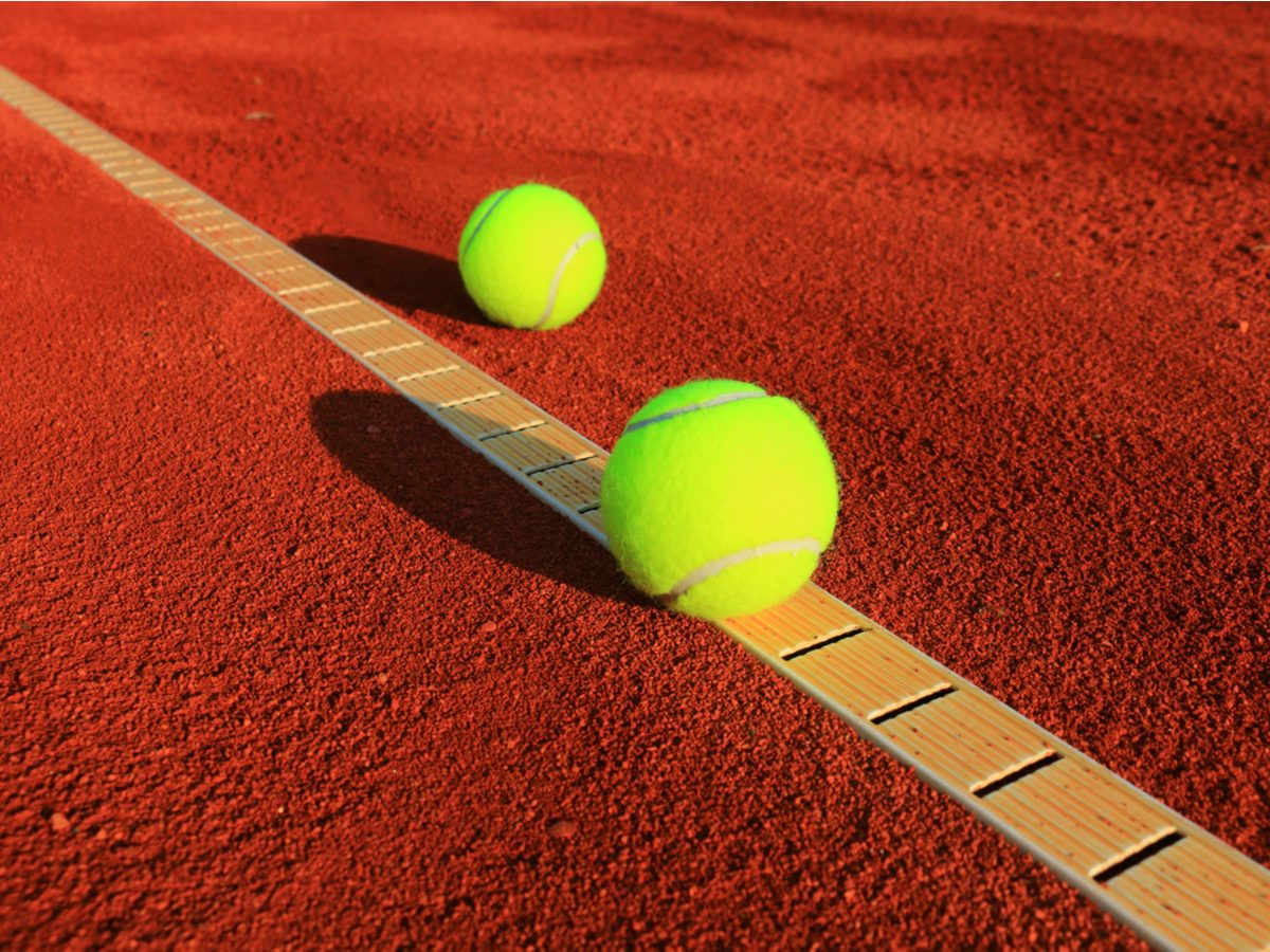 Yellow tennis balls on clay courts
