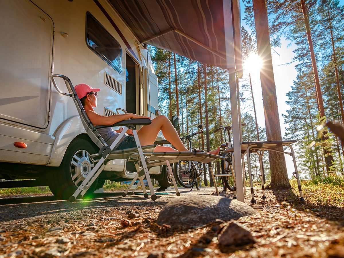 RV trip planner - woman lounging in folding chair beside RV motorhome